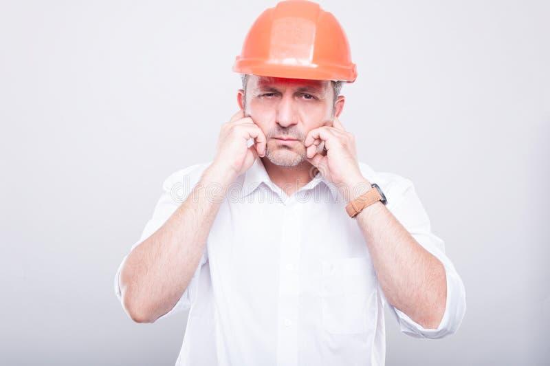 Πορτρέτο του αναδόχου που φορά hardhat που καλύπτει τα αυτιά του στοκ φωτογραφία