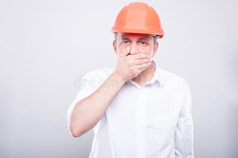Πορτρέτο του αναδόχου που φορά hardhat που καλύπτει το στόμα του στοκ εικόνες