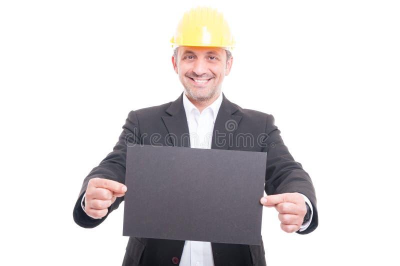 Πορτρέτο του αναδόχου που φορά hardhat που κρατά το γκρίζο χαρτόνι στοκ φωτογραφίες