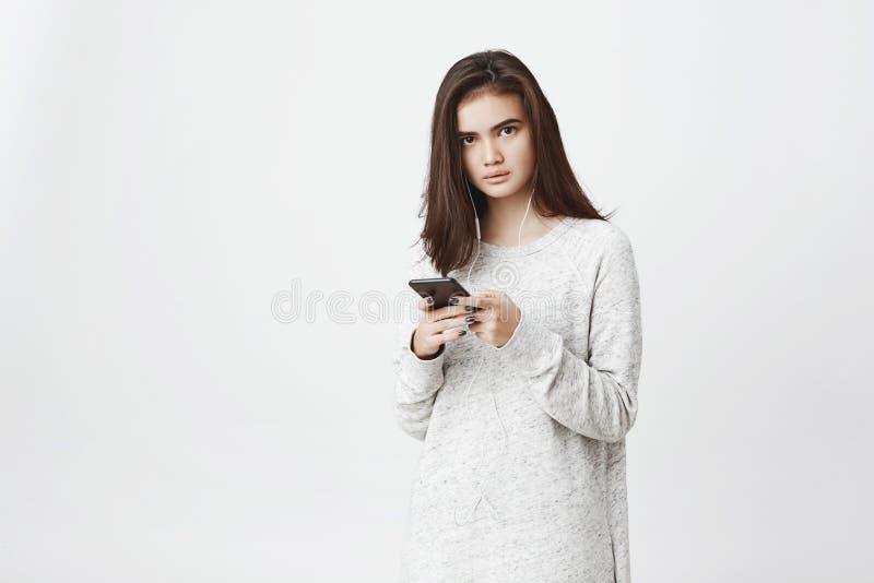 Πορτρέτο του ανησυχημένου και ματαιωμένου χαριτωμένου ευρωπαϊκού σπουδαστή, που κρατά το smartphone και που φορά τα ακουστικά, πέ στοκ εικόνα με δικαίωμα ελεύθερης χρήσης