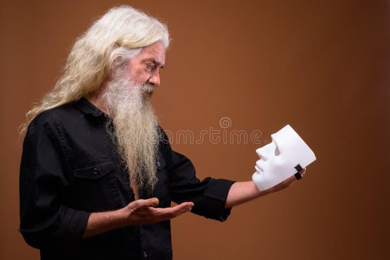Πορτρέτο του ανώτερου γενειοφόρου ατόμου που κρατά την άσπρη μάσκα στοκ εικόνες με δικαίωμα ελεύθερης χρήσης