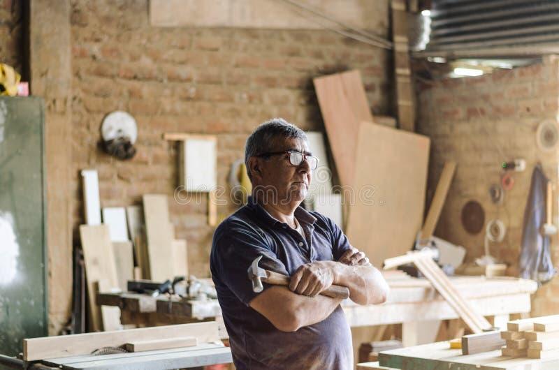 Πορτρέτο του ανώτερου ξυλουργού Στάση στο εργαστήριό του στοκ εικόνες