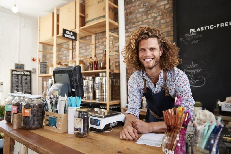 Πορτρέτο του αρσενικού ιδιοκτήτη του βιώσιμου πλαστικού ελεύθερου μανάβικου πίσω από το γραφείο πωλήσεων στοκ εικόνες