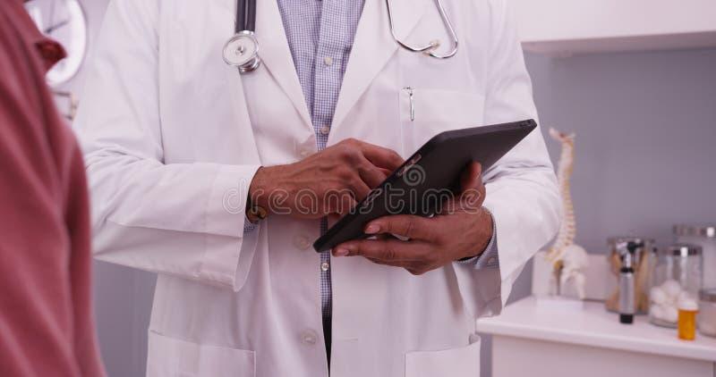 Πορτρέτο του αρσενικού μαύρου γιατρού που χρησιμοποιεί τη συσκευή ταμπλετών με ένα elderl στοκ φωτογραφία με δικαίωμα ελεύθερης χρήσης