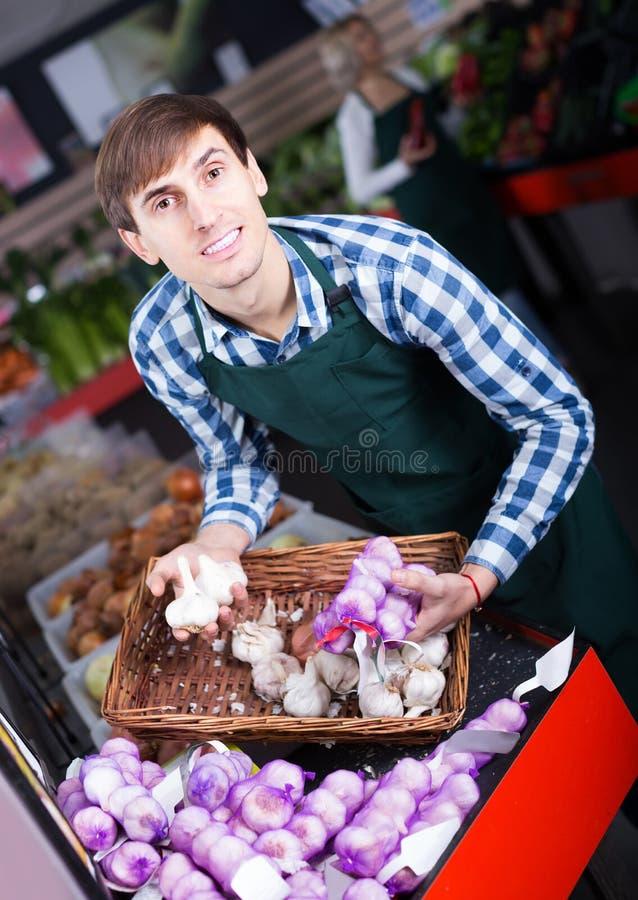 Πορτρέτο του αρσενικού πωλητή με τους μίσχους του σκόρδου στο παντοπωλείο στοκ φωτογραφία με δικαίωμα ελεύθερης χρήσης