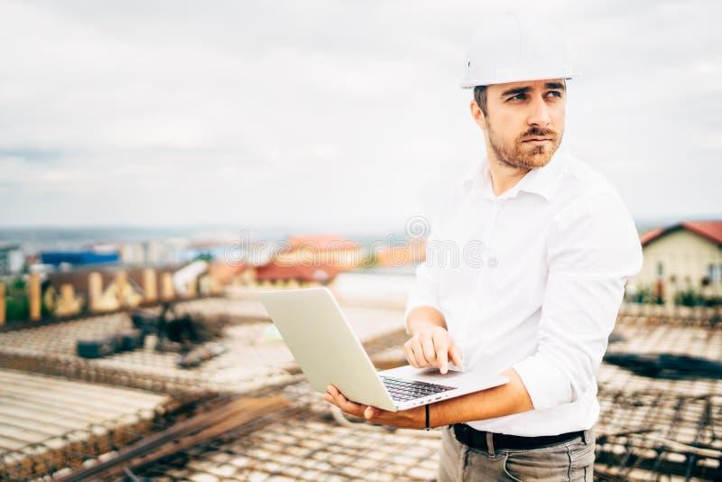Πορτρέτο του αρχιτέκτονα που χρησιμοποιεί το lap-top για το εργοτάξιο οικοδομής Εργαζόμενος στην περιοχή στοκ εικόνες με δικαίωμα ελεύθερης χρήσης