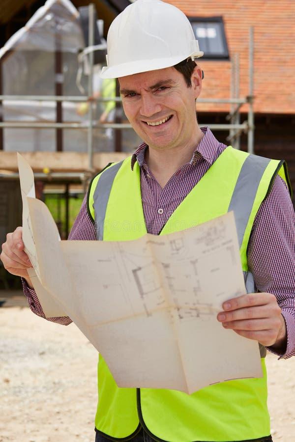 Πορτρέτο του αρχιτέκτονα στο εργοτάξιο που εξετάζει τα σχέδια σπιτιών στοκ φωτογραφία