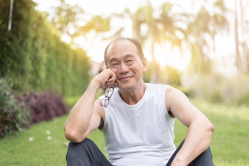 Πορτρέτο του ασιατικού ανώτερου ατόμου που χαλαρώνει και που κάθεται στη χλόη στο θόριο στοκ φωτογραφίες