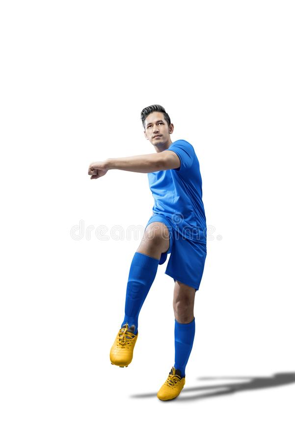 Πορτρέτο του ασιατικού ατόμου ποδοσφαιριστών στο μπλε Τζέρσεϋ με το λάκτισμα της θέσης σφαιρών στοκ εικόνες