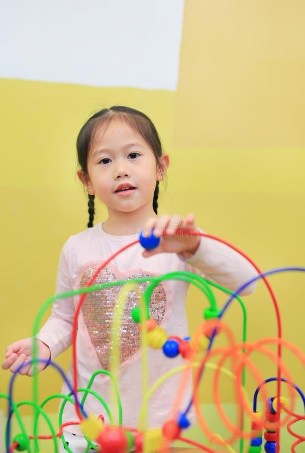 Πορτρέτο του ασιατικού κοριτσιού παιδιών που παίζει το εκπαιδευτικό παιχνίδι για την ανάπτυξη εγκεφάλου στο δωμάτιο παιδιών στοκ φωτογραφίες