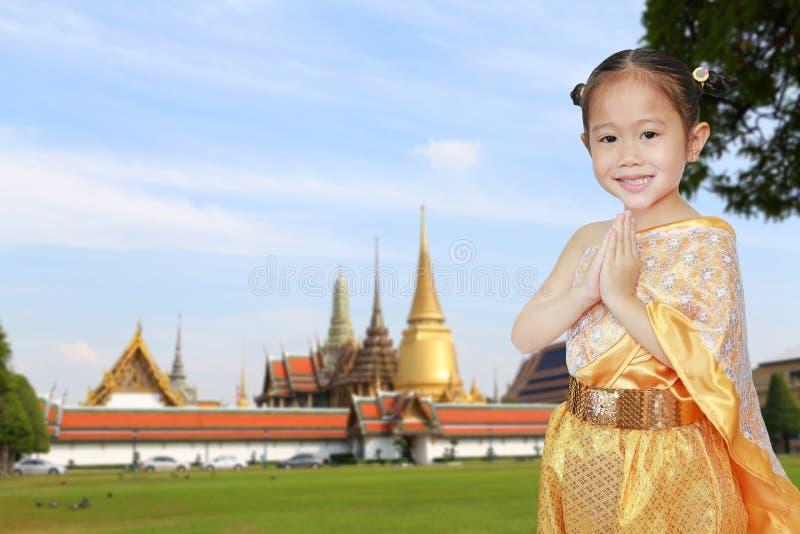 Πορτρέτο του ασιατικού κοριτσιού παιδιών στο παραδοσιακό ταϊλανδικό φόρεμα που προσεύχεται ενάντια στο μεγάλα παλάτι και Wat Phra στοκ φωτογραφίες με δικαίωμα ελεύθερης χρήσης