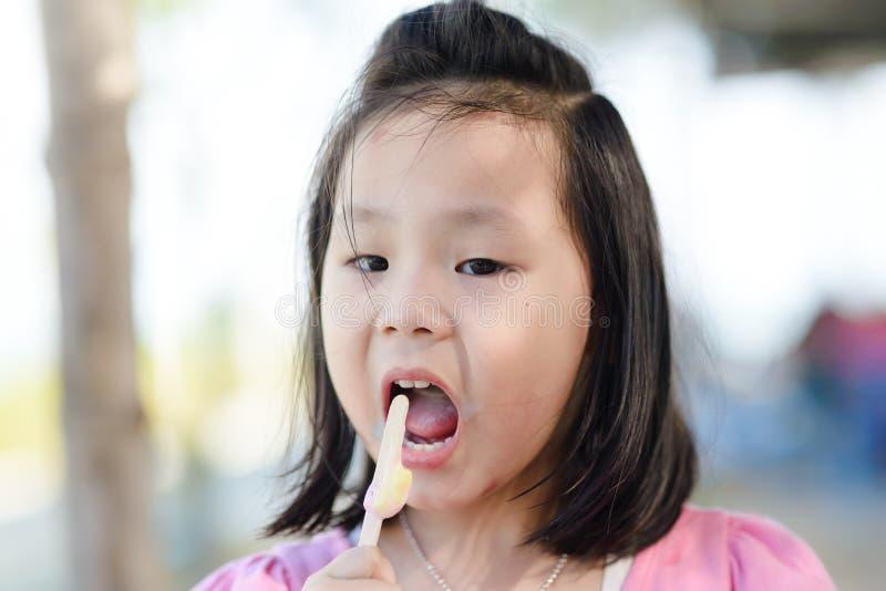 Πορτρέτο του ασιατικού κοριτσιού που τρώει ένα παγωτό στοκ εικόνες