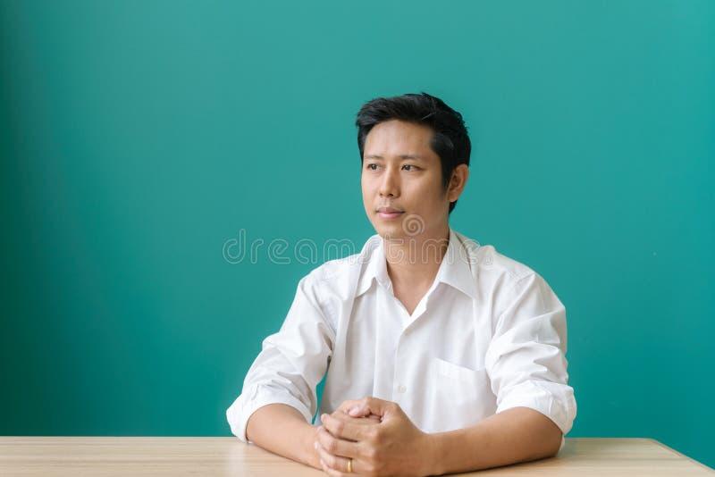Πορτρέτο του ασιατικού χαμόγελου επιχειρηματιών και της εξέτασης τη κάμερα με το χαμόγελο καθμένος στη θέση εργασίας μπλε τοίχου  στοκ φωτογραφία