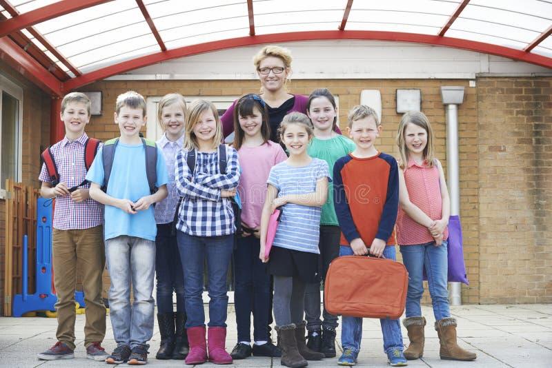 Πορτρέτο του δασκάλου με τους μαθητές στην παιδική χαρά στοκ φωτογραφίες
