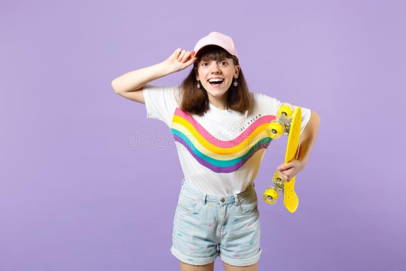 Πορτρέτο του αστείου κοριτσιού εφήβων στα ζωηρά ενδύματα που φαίνεται κάμερα, που κρατά κίτρινο skateboard απομονωμένο στην ιώδη  στοκ εικόνα με δικαίωμα ελεύθερης χρήσης