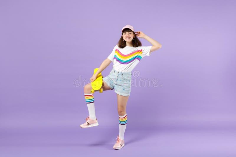Πορτρέτο του αστείου κοριτσιού εφήβων στα ζωηρά ενδύματα που στέκονται, που κρατά κίτρινο skateboard απομονωμένο στον ιώδη τοίχο  στοκ φωτογραφίες με δικαίωμα ελεύθερης χρήσης