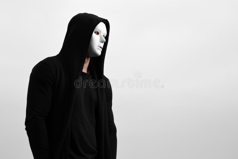 Πορτρέτο του ατόμου στο μαύρο hoodie που φορά την άσπρη ανώνυμη μάσκα στοκ φωτογραφία με δικαίωμα ελεύθερης χρήσης