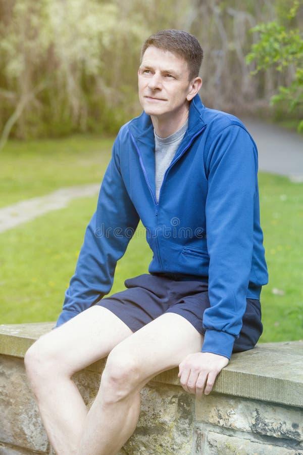 Πορτρέτο του ατόμου sportswear στη συνεδρίαση υπαίθρια στοκ φωτογραφία με δικαίωμα ελεύθερης χρήσης