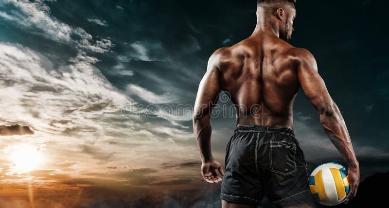 Πορτρέτο του αφροαμερικανού αθλητικού τύπου, φορέας πετοσφαίρισης παραλιών με μια σφαίρα πέρα από το υπόβαθρο ουρανού Κατάλληλος  στοκ εικόνες