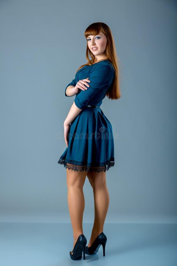Πορτρέτο του α συν τη θηλυκή redhead πρότυπη τοποθέτηση μεγέθους στο μπλε φόρεμα πέρα από το γκρίζο υπόβαθρο Όμορφη γυναίκα με το στοκ φωτογραφίες