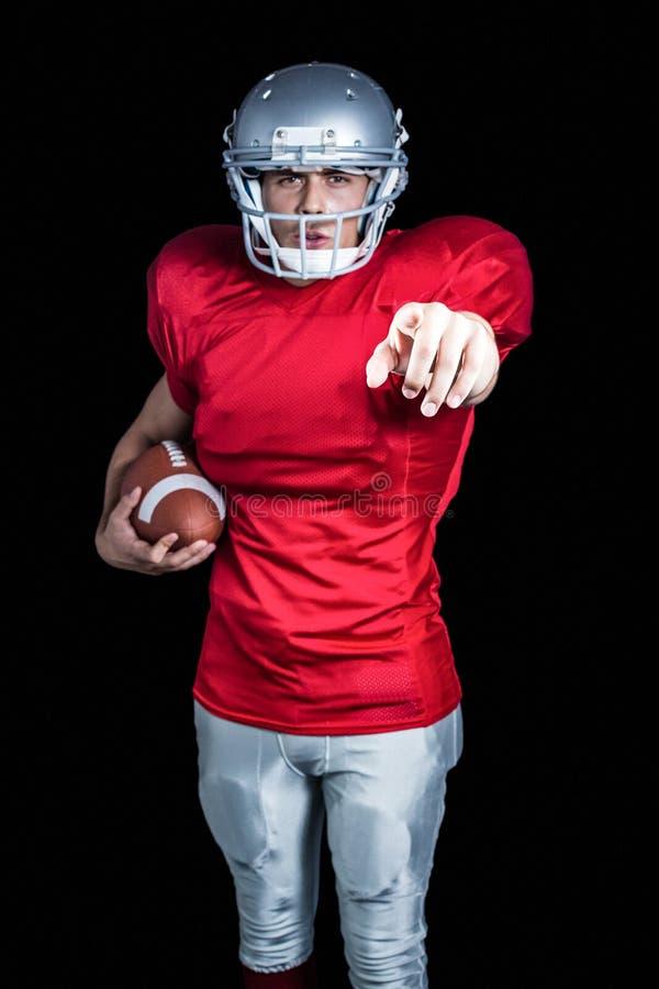 Πορτρέτο του βέβαιου αθλητικού τύπου που δείχνει κρατώντας το αμερικανικό ποδόσφαιρο στοκ φωτογραφία