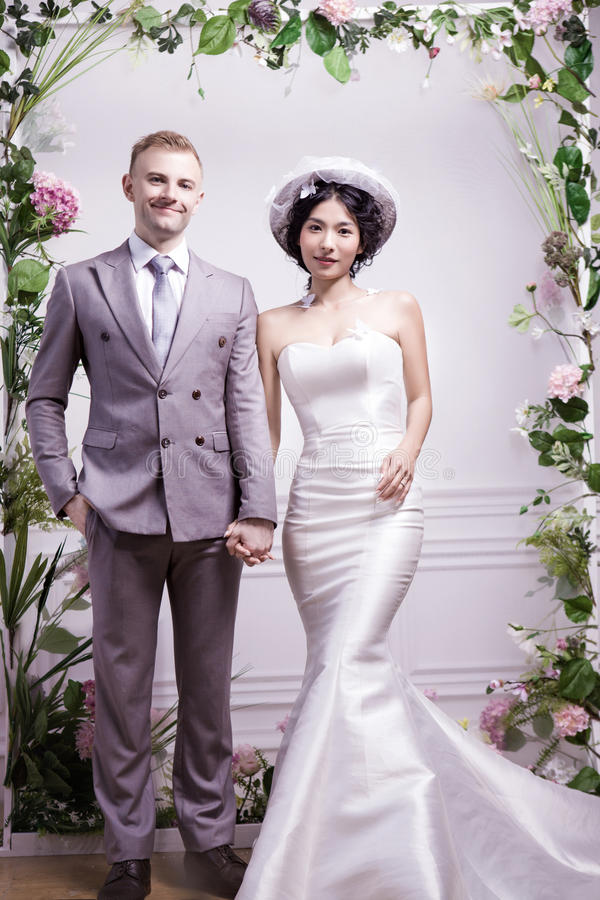 Πορτρέτο του βέβαιου γαμήλιου ζεύγους που στέκεται ενάντια στον άσπρο τοίχο στοκ φωτογραφία