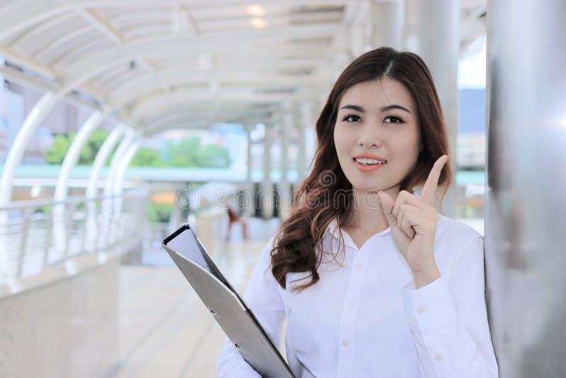 Πορτρέτο του βέβαιου νέου ασιατικού φακέλλου και της εξέτασης εγγράφων εκμετάλλευσης επιχειρησιακών γυναικών τη κάμερα στο εξωτερ στοκ εικόνες