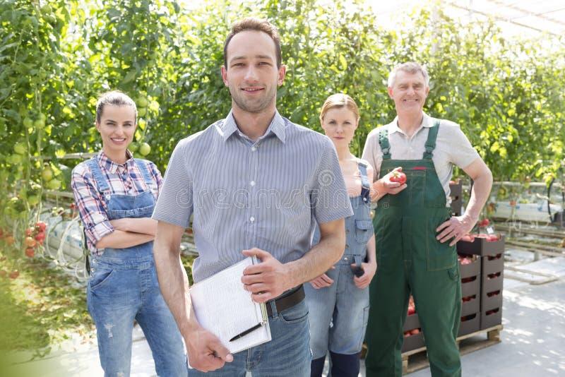 Πορτρέτο του βέβαιων επόπτη και των κηπουρών που στέκονται στο θερμοκήπιο στοκ εικόνα με δικαίωμα ελεύθερης χρήσης
