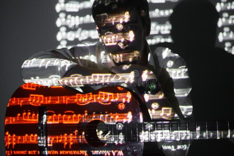 Πορτρέτο του γενειοφόρου κιθαρίστα με την προβολή των σημειώσεων Manis που κρατά την κιθάρα του και που εξετάζει τη κάμερα στοκ εικόνες