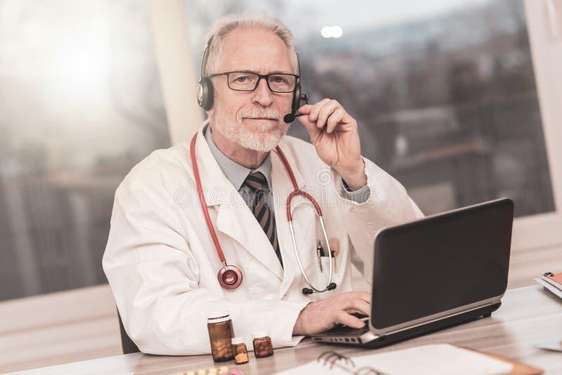 Πορτρέτο του γιατρού κατά τη διάρκεια των σε απευθείας σύνδεση ιατρικών διαβουλεύσεων στοκ φωτογραφία