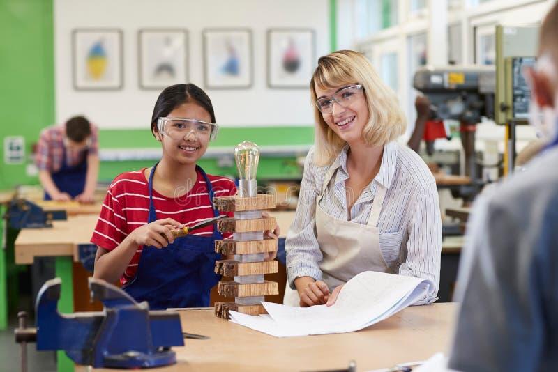 Πορτρέτο του δασκάλου που βοηθά το θηλυκό κτήριο σπουδαστών γυμνασίου στοκ εικόνα με δικαίωμα ελεύθερης χρήσης