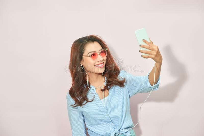 Πορτρέτο του δροσερού εύθυμου κοριτσιού που έχει την τηλεοπτικός-κλήση με τον εραστή που κρατά τον έξυπνο πυροβολισμό τηλεφωνικών στοκ φωτογραφίες με δικαίωμα ελεύθερης χρήσης