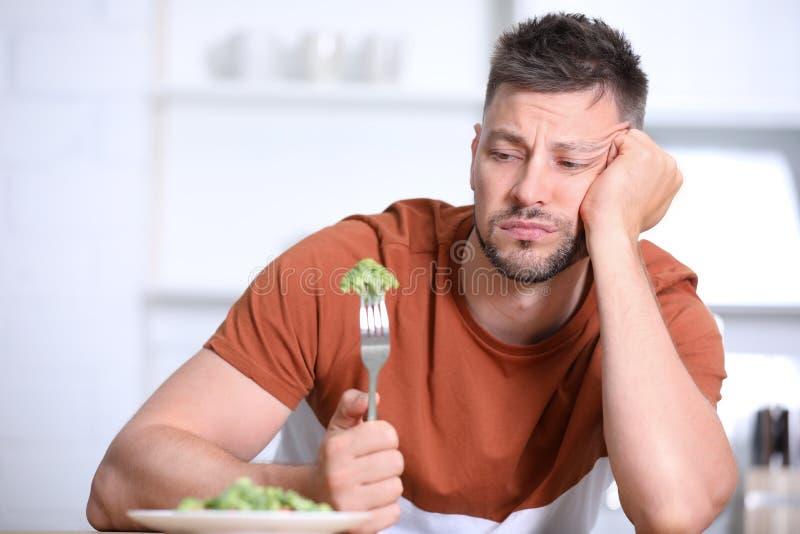 Πορτρέτο του δυστυχισμένου ατόμου που τρώει τη σαλάτα μπρόκολου στοκ φωτογραφία με δικαίωμα ελεύθερης χρήσης
