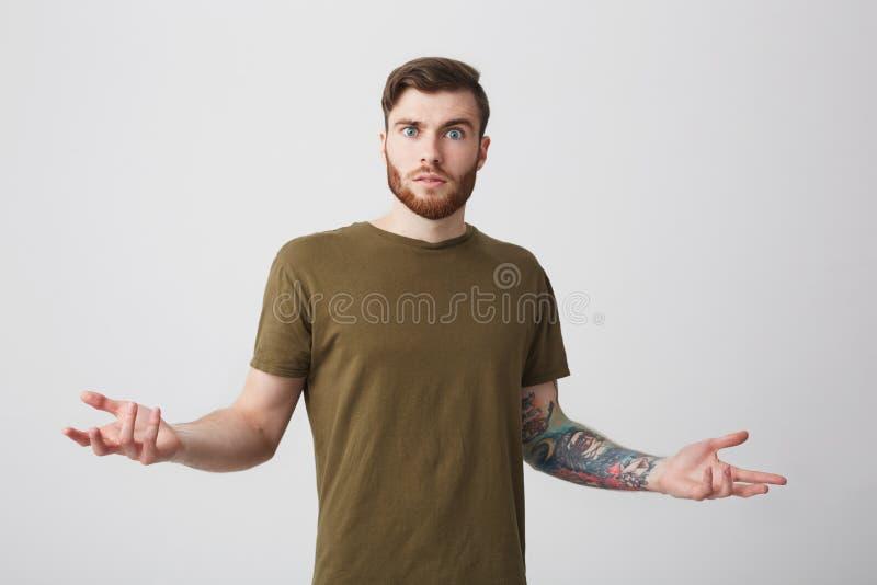 Πορτρέτο του δυστυχισμένου ελκυστικού γενειοφόρου διαστισμένου καυκάσιου ατόμου με την κοντή σκοτεινή τρίχα στα καφετιά χέρια διά στοκ εικόνα με δικαίωμα ελεύθερης χρήσης