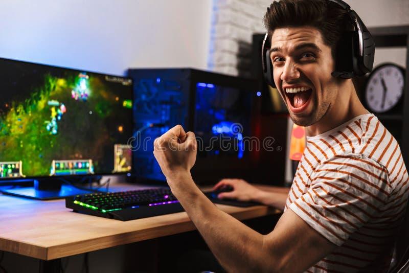 Πορτρέτο του εκστατικού τύπου gamer στην κραυγή και το rejoi ακουστικών στοκ εικόνα