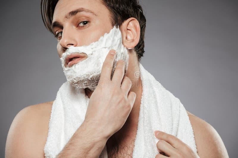 Πορτρέτο του ελκυστικού ατόμου με την πετσέτα στο λαιμό που βάζει τα ξυρίζοντας FO στοκ φωτογραφία με δικαίωμα ελεύθερης χρήσης