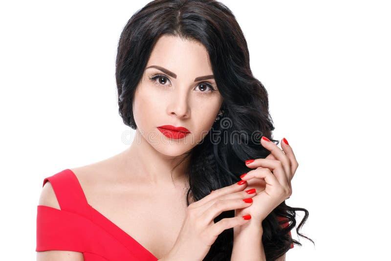 Πορτρέτο του ελκυστικού κοριτσιού brunette με τα κόκκινα χείλια και τα κόκκινα καρφιά η ανασκόπηση απομόνωσε το λευκό στοκ φωτογραφίες