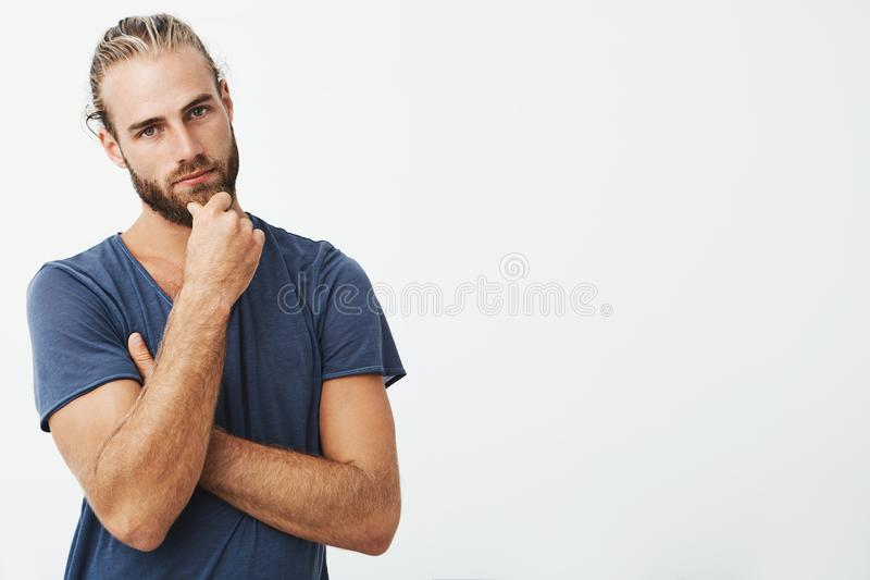 Πορτρέτο του ελκυστικού νεαρού άνδρα με το μοντέρνο χέρι εκμετάλλευσης hairstyle στο πηγούνι με τη στοχαστική έκφραση, που κοιτάζ στοκ εικόνα με δικαίωμα ελεύθερης χρήσης