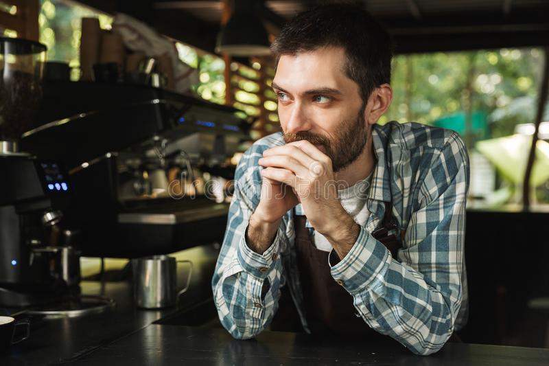 Πορτρέτο του ελκυστικού τύπου barista που χαμογελά λειτουργώντας στον καφέ ή το καφέ οδών υπαίθριο στοκ εικόνα