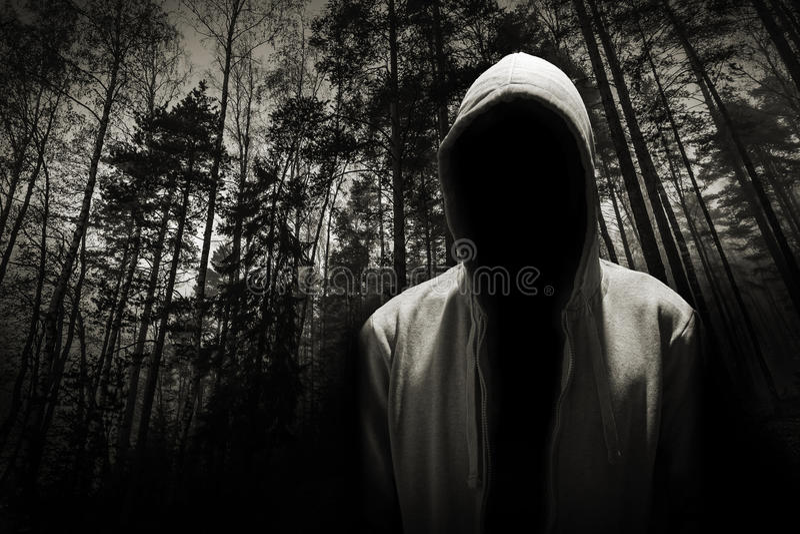 Πορτρέτο του επικίνδυνου ατόμου κάτω από την κουκούλα στο δάσος στοκ εικόνες