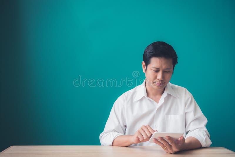 Πορτρέτο του επιχειρηματία που χαμογελά και που χρησιμοποιεί το μαξιλάρι στον υπολογιστή γραφείου ενάντια του μπλε τοίχου στοκ εικόνες με δικαίωμα ελεύθερης χρήσης