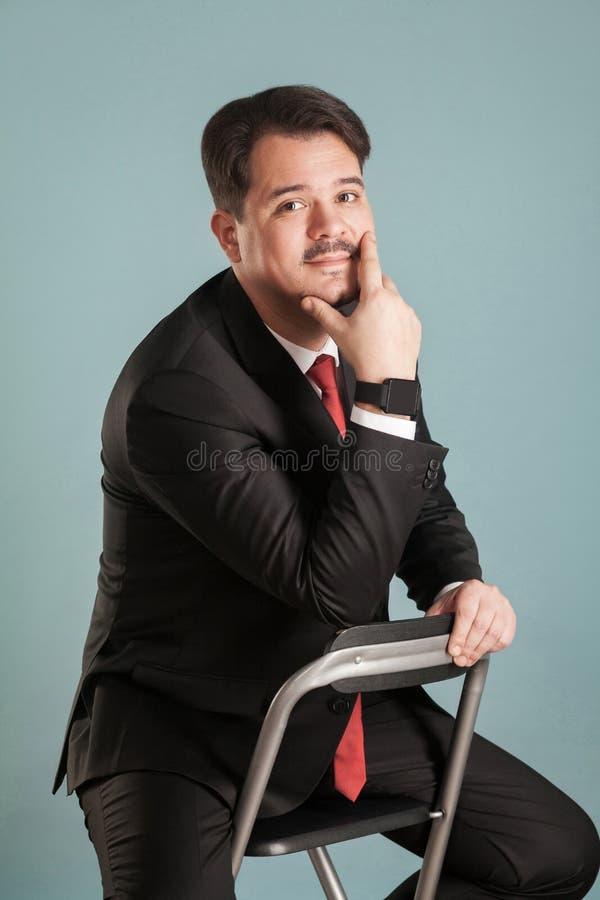 Πορτρέτο του επιχειρησιακού ατόμου, που εξετάζει τη κάμερα και λίγο χαμόγελο στοκ φωτογραφία