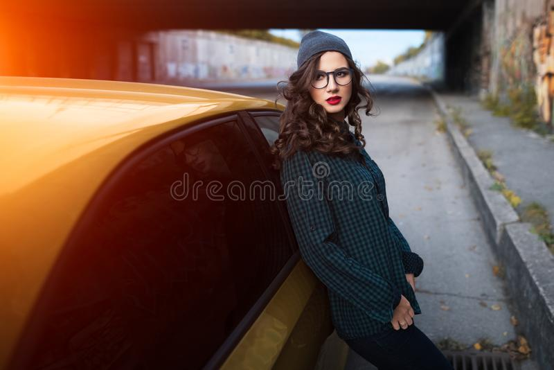 Πορτρέτο του ευρωπαϊκού σγουρού κοριτσιού με τα γυαλιά, κοντά στο κίτρινο αυτοκίνητο υπαίθριο στοκ εικόνες