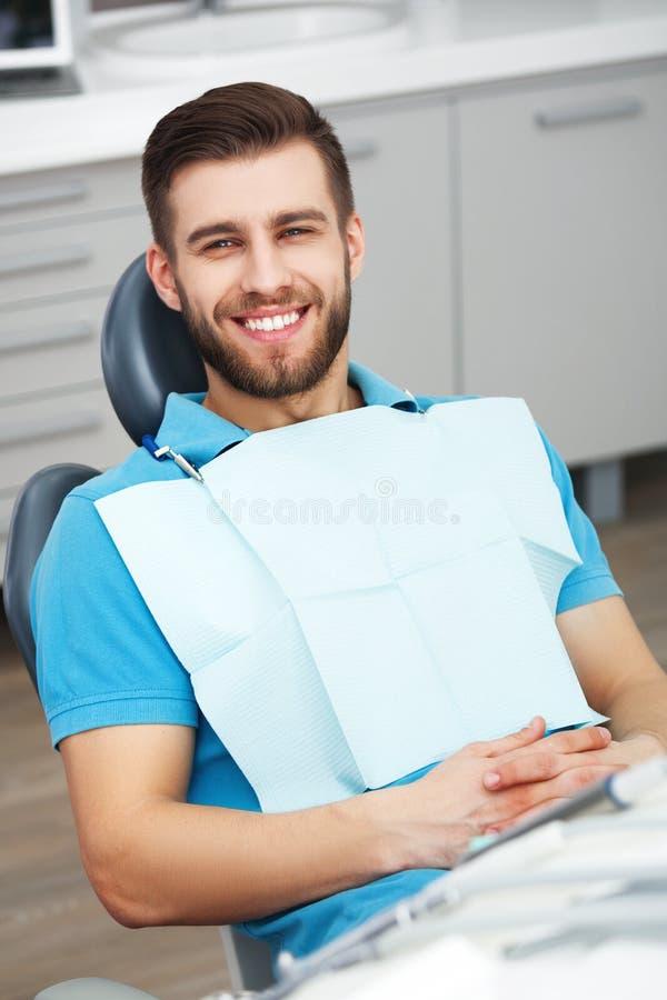 Πορτρέτο του ευτυχούς ασθενή στην οδοντική καρέκλα στοκ εικόνες