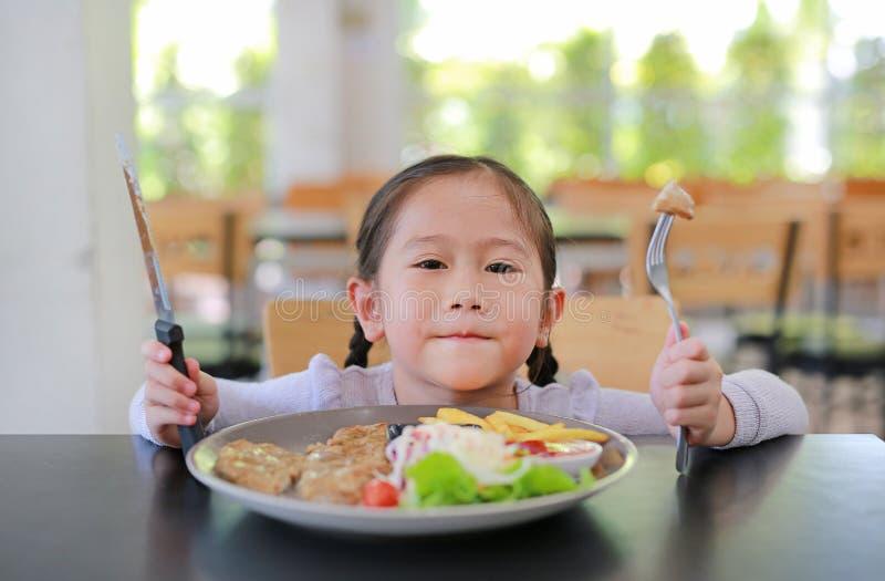 Πορτρέτο του ευτυχούς ασιατικού κοριτσιού παιδιών που τρώει την μπριζόλα χοιρινού κρέατος και τη φυτική σαλάτα στον πίνακα με το  στοκ εικόνες