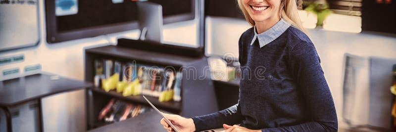 Πορτρέτο του ευτυχούς δασκάλου που χρησιμοποιεί το lap-top στην τάξη στοκ φωτογραφία