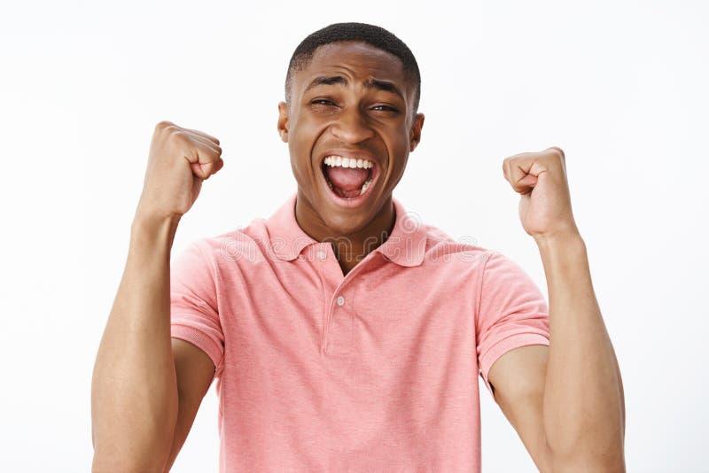 Πορτρέτο του ευτυχούς ευχαριστημένου και κατάπληκτου ελκυστικού αρσενικού ανεμιστήρα αφροαμερικάνων που αυξάνει τα χέρια με τις σ στοκ εικόνες
