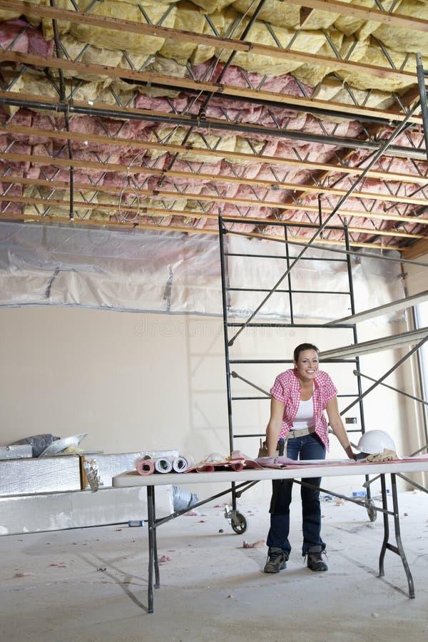 Πορτρέτο του ευτυχούς θηλυκού αναδόχου με την οικοδόμηση των σχεδίων στοκ εικόνα με δικαίωμα ελεύθερης χρήσης