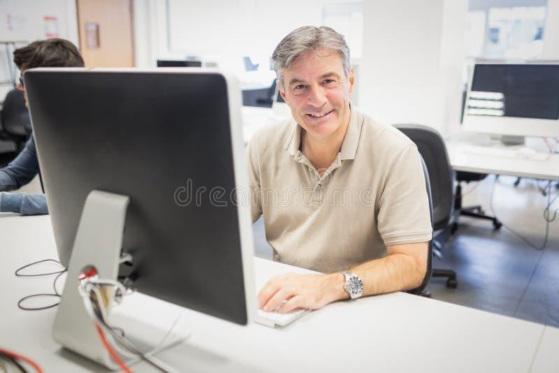 Πορτρέτο του ευτυχούς καθηγητή που εργάζεται στον υπολογιστή στοκ φωτογραφία