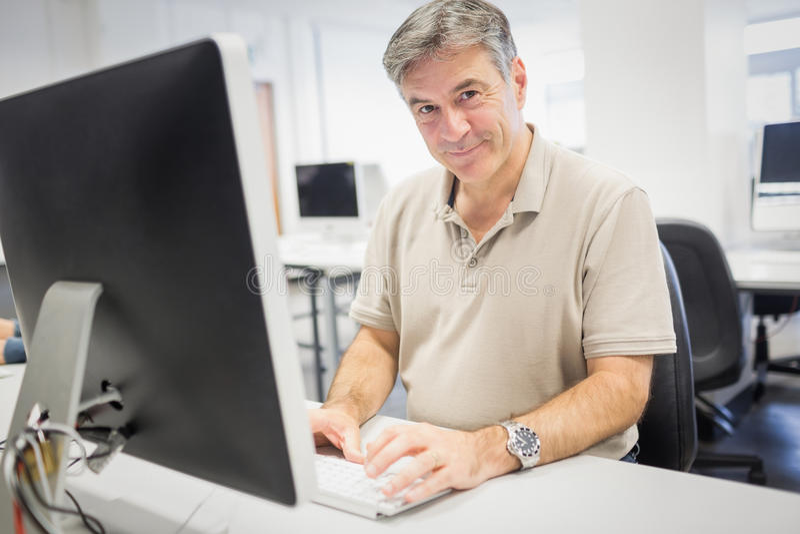 Πορτρέτο του ευτυχούς καθηγητή που εργάζεται στον υπολογιστή στοκ φωτογραφίες με δικαίωμα ελεύθερης χρήσης